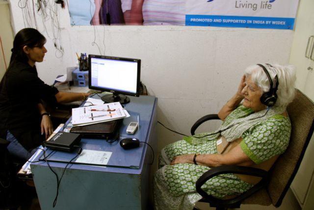 Elderly woman getting her hearing tested (wearing headphones)