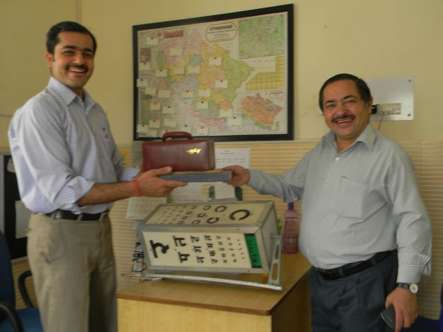 One man handing a hearing test instrument to another - all smiles!