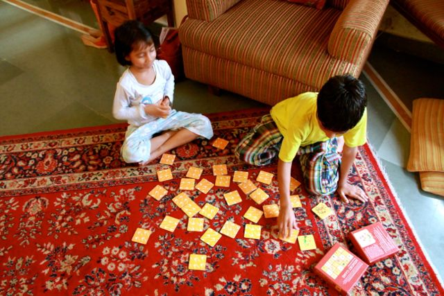 Two Indian children playing Memory Game, all the cards scattered helter-skelter on the rug