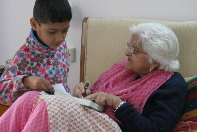 Little boy stands beside an elderly teacher who is checking his work