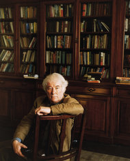 White haired Irish poet in book-lined room