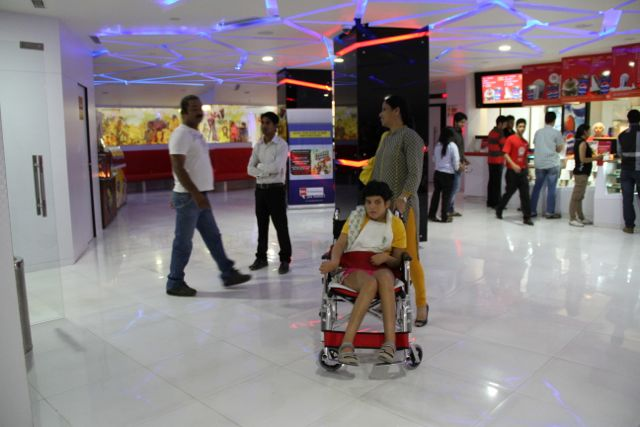 Girl in wheelchair waits in theatre lobby with a woman
