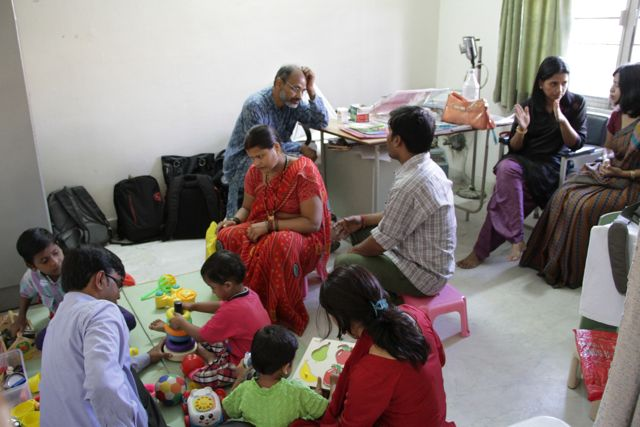 Group - some on the floor (children, health workers); some in chairs