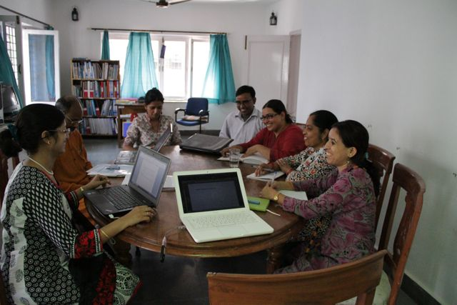 Group of people in India sitting around a table, laptops open