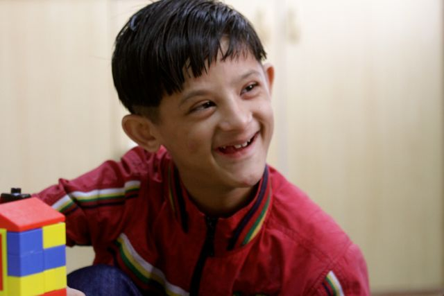 Boy with down Syndrome, smiling fetchingly
