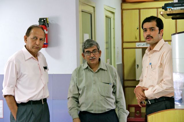 Three men in a row, standing in an early intervention centre