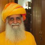 Indian man with long white beard, wearing orange kurta and orange turban