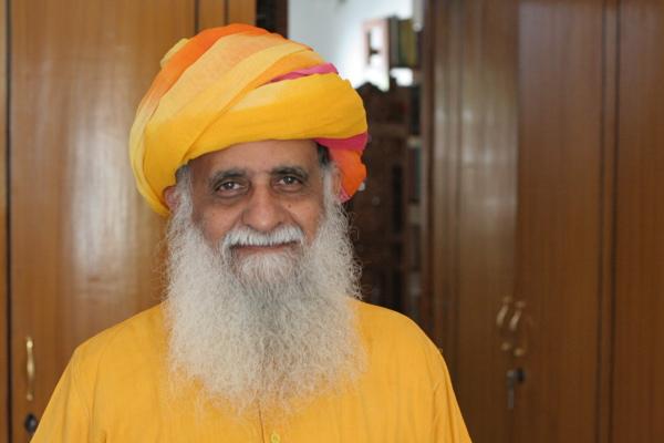 Bearded Indian man in saffron kurta and multi-colored turban