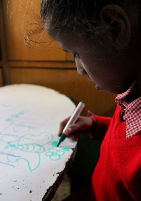 Young girl drawing a picture on a table top