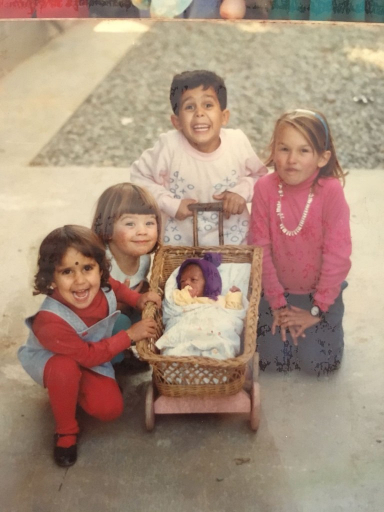 Four children gather round a baby in a doll's stroller