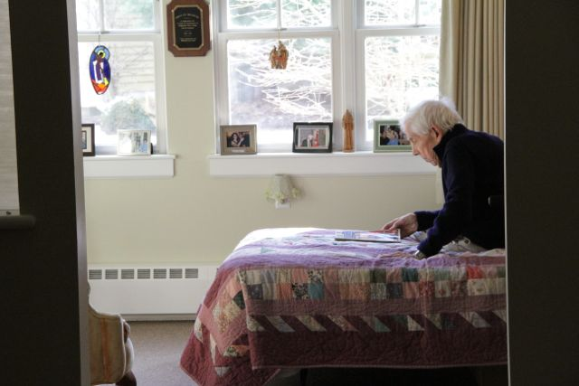 Elderly man sitting on his bed, surrounded by photos, reading