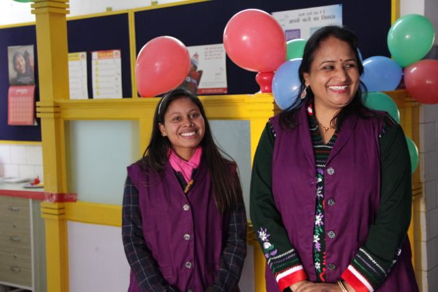 Tow women in purple smocks, standing in front of balloons!