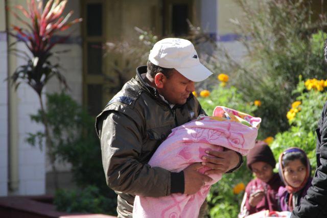 Indian man gazing down at his newborn baby girl