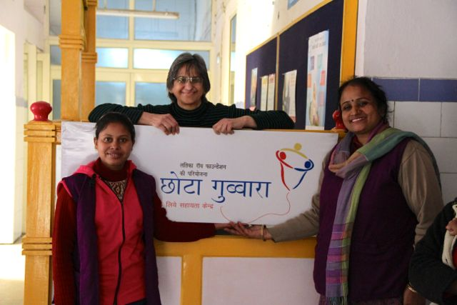 Three women clustered around centre for high risk newborns; sign for Chhota Gubbara in the middle
