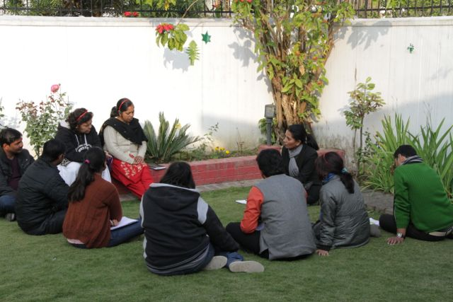 Group of CBR workers sit on lawn in a planning meeting