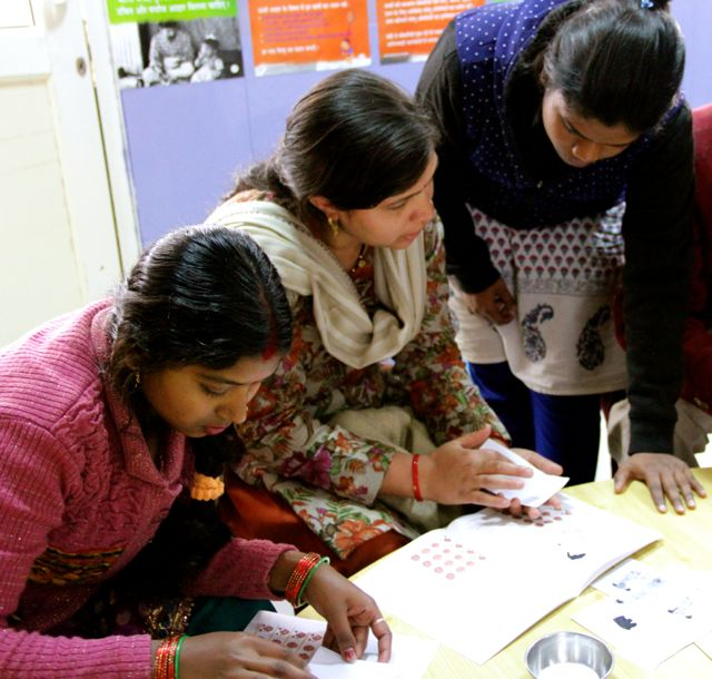 a therapists helps two mothers to insert picture-advices in the booklet