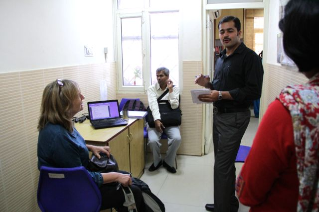 British woman and blind Indian man sit at desks, looking up at two Foundation staff