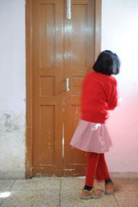 Girl in red standing near a brown door looking away