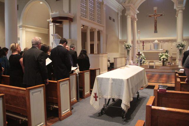 Funeral in a church; coffin in aisle, mourners all in black