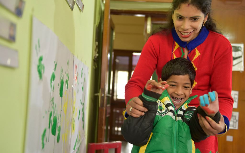 Teacher helping a happy child with cerebral palsy paint on a wall