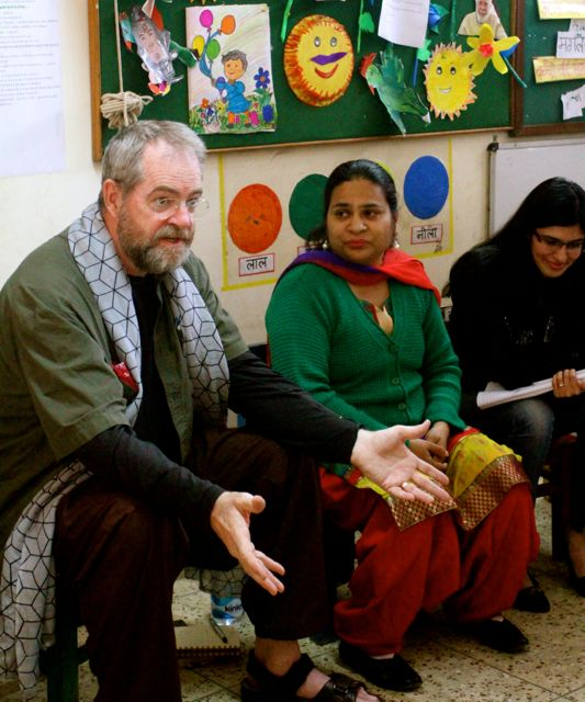 Man telling a story in children's classroom; women listening