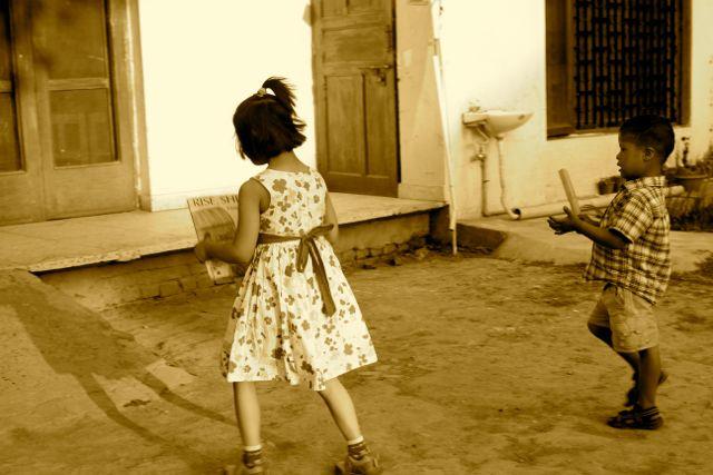 Girl and boy walking toward a building; girl holding a book