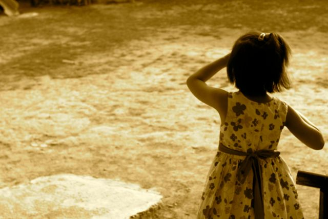 Small girl in white frock, seen from behind, looking out over a sepia-toned expanse