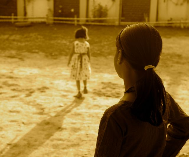 Little girl in sepia-toned field; older girl stands watching; both seen from behind