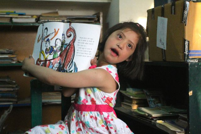A little girl with Down Syndrome holds a book up, wide open, showing a brightly colored drawing
