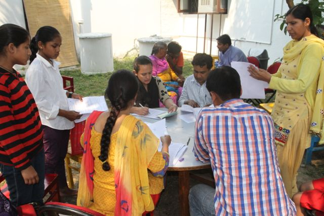 People around a round table, filling out forms