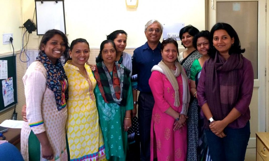 Eight colourfully dressed Indian women, standing with one Indian man - all smiling broadly