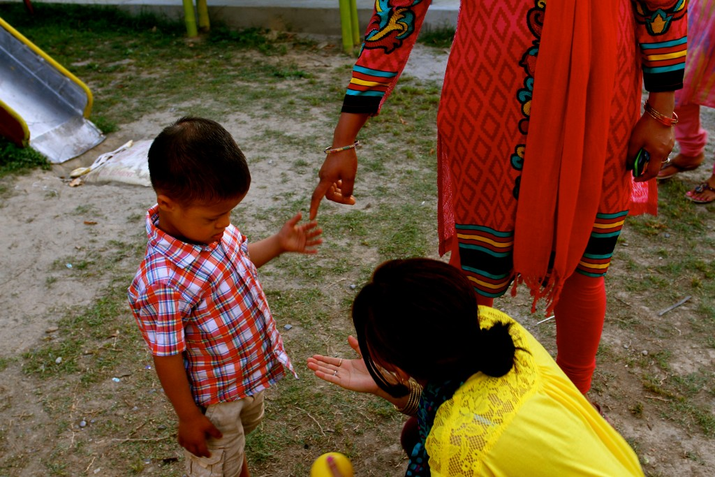 Child with Down Syndrome holding his mother's hand, meeting a teacher