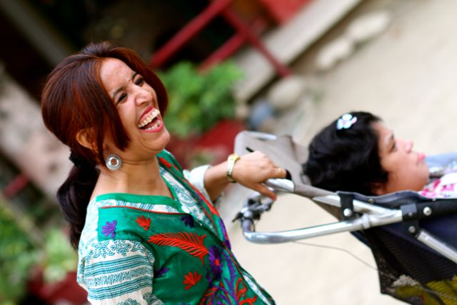 Smiling woman with disabled child in a stroller