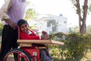 Smiling boy in wheelchair being pushed by a man whose face cannot be seen