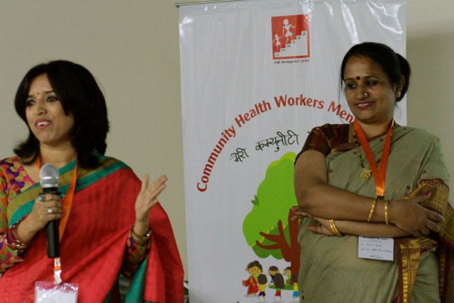 """Two women in front of a sign reading """"Community Health Workers' Meeting"""""""