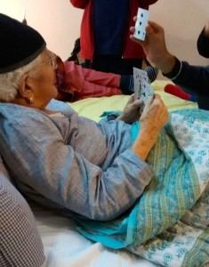 Elderly woman playing cards on her death bed