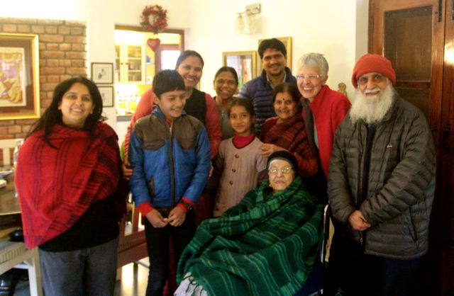 A family group photo with elderly woman in front in a wheelchair