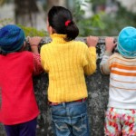Three children, backs to the camera, peek out over a wall