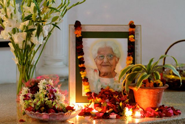 Picture of elderly Indian woman, with a garland around the photo and flowers and lit candles in front of it