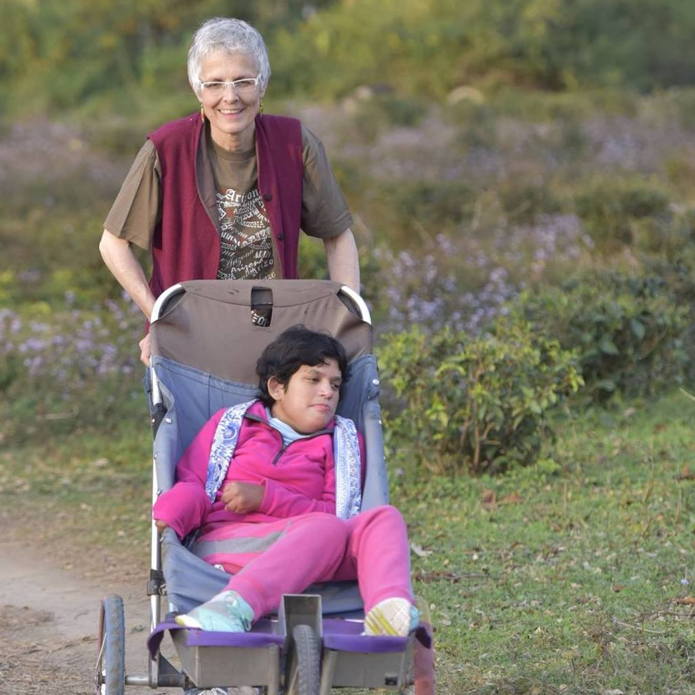 White haired woman pushes young handicapped woman in a blue stroller