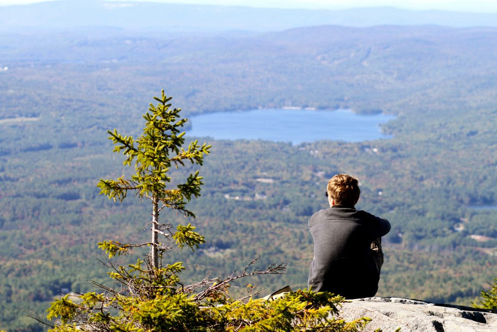 Man sitting on the edge of a mountain, looking out over a vast vista