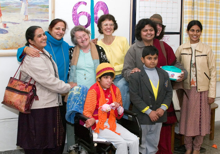 Group photo of smiling women, girl in wheelchair in front and boy in school uniform