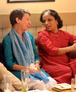 Indian woman in red talks with British woman in blue