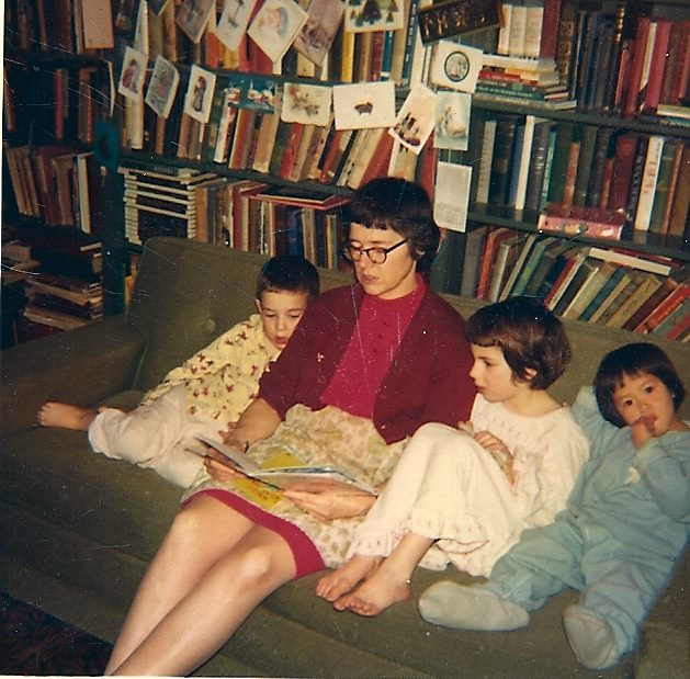 Mom on a couch, reading a story to with three children