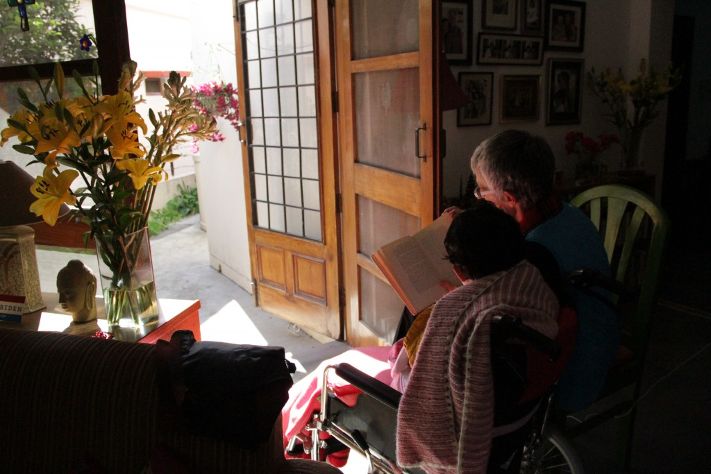 View from the bak of a mother reading to a child in a wheelchair