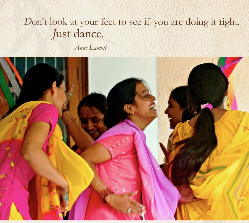 Indian women in colourful pink and yellow outfits, dancing in a circle