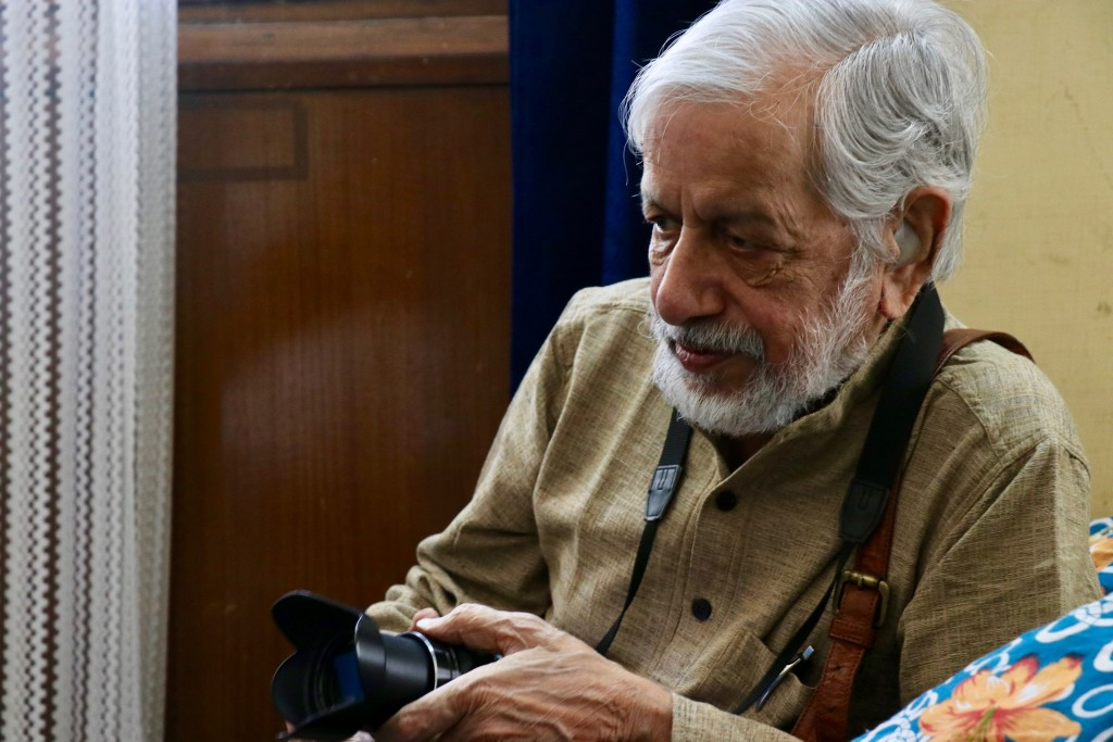White-haired Indian man with a camera, watching from the side