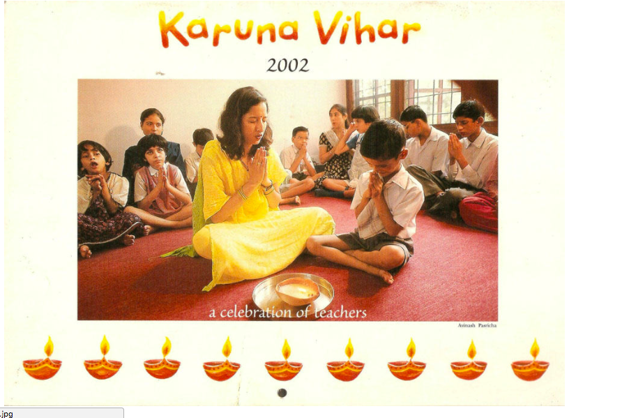 Teacher in yello sari, praying with disabled children