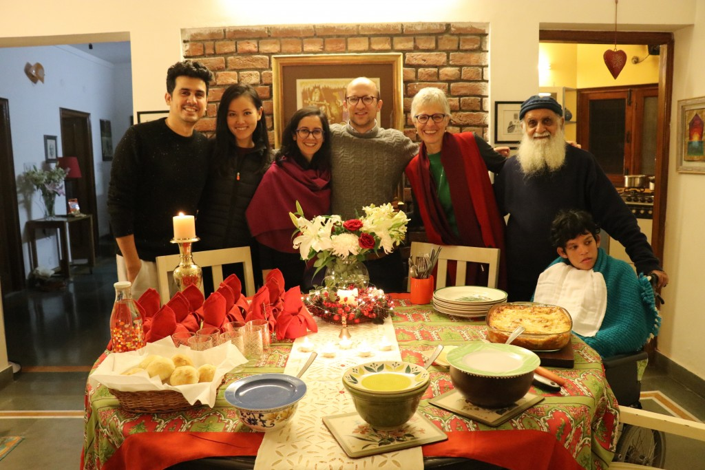 Family of seven (older parents, two young cuples, one girl in wheelchair) around a Christmas table