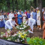 Large crowd of Indians, dressed in colourful clothes, in a cemetery. Young man and woman in white laying a wreath on the grave.